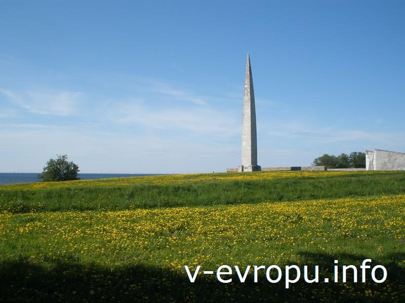 Советский военный монумент устремляется в небо посреди цветущего поля