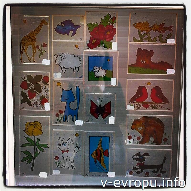 В окне мастерской выставлены расписанные вручную стекла для детских ночников