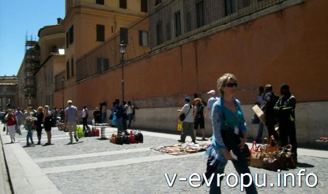 Рядом с Музеями Ватикана уличные торговцы продают безделушки, сувениры, брэндовые подделки