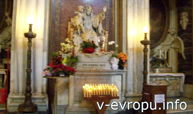 Скульптура Девы Марии и электрические свечи в церкви Рима Санта Мария Маджоре