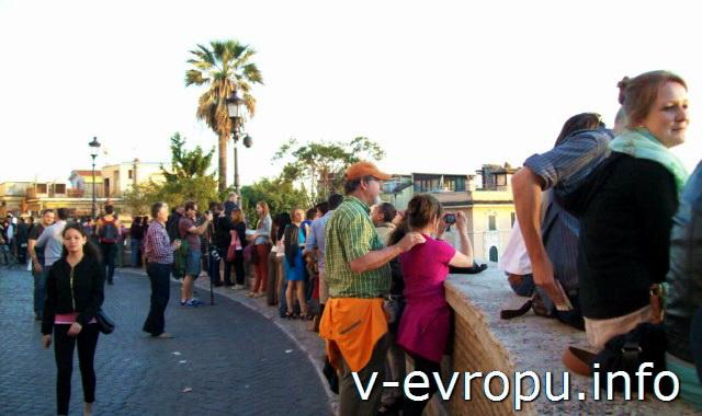 Туристы встречают весенний вечер   на вершине Испанской Лестницы у церкви Тринити-деи-Монти в Риме